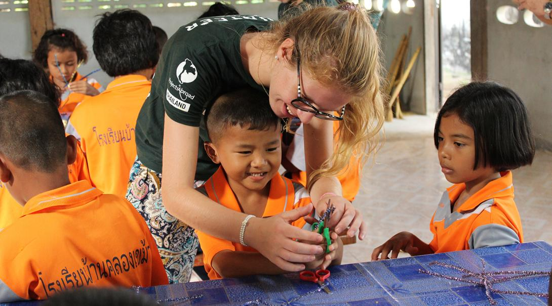 Lärarvolontär hjälper en liten elev med dennes skoluppgift i Kambodja